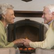 Couple sitting in living room by fireplace holding hands and smi — Stock Photo #4764865