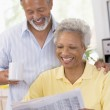 Couple relaxing with a newspaper smiling — Stock Photo