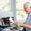 Man in home office with paperwork and computer — Stock Photo