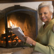 Woman sitting in living room by fireplace with newspaper smiling - Stock Photo
