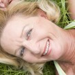Woman lying in grass smiling — Stock Photo