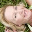 Woman lying in grass smiling - Stock Photo