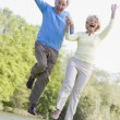 Foto Stock: Couple jumping outdoors at park by lake smiling