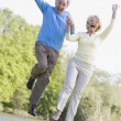 Couple jumping outdoors at park by lake smiling — Zdjęcie stockowe #4764999