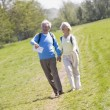 Couple walking on path in park holding hands and smiling — ストック写真