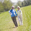 Couple walking on path in park holding hands and smiling - Stock Photo