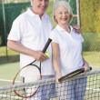 Couple playing tennis and smiling — Stock Photo