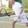 Man playing tennis and smiling - Stock Photo