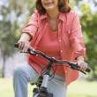 Woman on bike outdoors smiling — Stock Photo #4765065