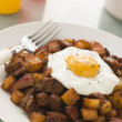 Corned Beef Hash With a Fried Egg and Black Pepper - Lizenzfreies Foto