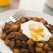 Corned Beef Hash with a Broken Fried Egg and Black Pepper - Lizenzfreies Foto