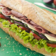 Deli Sub Sandwich on a Chopping Board - Stock fotografie