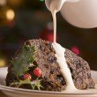 Portion of Christmas Pudding with Pouring Cream — Stock Photo #4765344