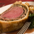 Slice of Beef Wellington with Spinach and Saut ed Potatoes - Stock Photo