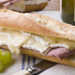 Brie and Ham Baguette with White Wine and Grapes - Stockfoto