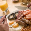 Eating a Full English Breakfast - Stock Photo