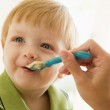 Mother feeding young boy baby food — Stock Photo