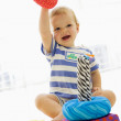 Baby indoors playing with soft toy — Stock Photo
