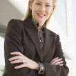 Businesswoman standing outdoors by building smiling — Lizenzfreies Foto