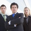 Three businesspeople standing outdoors by building — Stock Photo