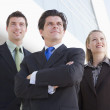 Three businesspeople standing outdoors by building smiling — Stock Photo