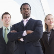 Three business standing outdoors by building smiling — Stock Photo