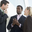 Three businesspeople standing outdoors by building talking and s — Stock Photo