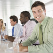 Four businesspeople in a boardroom smiling — Stock Photo