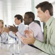 Four businesspeople in a boardroom applauding — Stockfoto #4766694