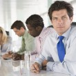 Stock Photo: Four businesspeople in boardroom writing