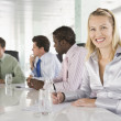 Four businesspeople in a boardroom smiling — Stock Photo #4766699