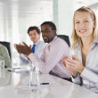 Four businesspeople in a boardroom applauding - Stockfoto
