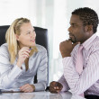 Two businesspeople in office talking — Stockfoto