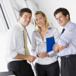 Three businesspeople standing in corridor smiling — Stock Photo