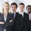 Four businesspeople standing in corridor smiling — Stock Photo #4766748
