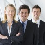Three businesspeople standing in corridor smiling — Stock Photo