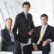 Three businesspeople sitting in office lobby - Stock Photo