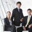 Stock Photo: Three businesspeople sitting in office lobby smiling