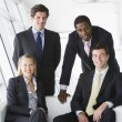 Four businesspeople in office lobby smiling - Stock Photo