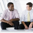 Two businessmen sitting in office lobby talking and smiling — Stock Photo #4766762