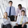 Four businesspeople in office lobby — Stock Photo
