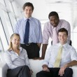 Four businesspeople in office lobby smiling — Stock Photo