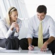 Two businesspeople sitting in office lobby talking and smiling — Stock Photo