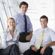 Three businesspeople sitting in office lobby smiling — Stock Photo