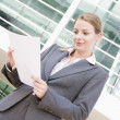 Businesswoman standing outdoors reading paperwork — Foto Stock