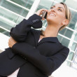 Businesswoman standing outdoors using cellular phone and smiling — Stock Photo