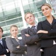 Four businesspeople standing outdoors smiling — Stock Photo #4766776