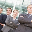 Four businesspeople standing outdoors smiling — Stock Photo #4766777