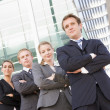Four businesspeople standing outdoors smiling — Stock Photo