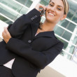 Businesswoman standing outdoors on cellular phone smiling — Foto Stock